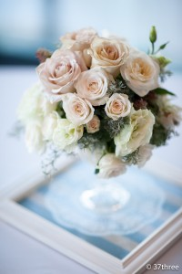 A vintage inspired centrepiece in footed crystal vase placed on whitewash frame and lace table runner