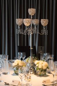 Petite posies in fishbowl vases surrounding candelabra